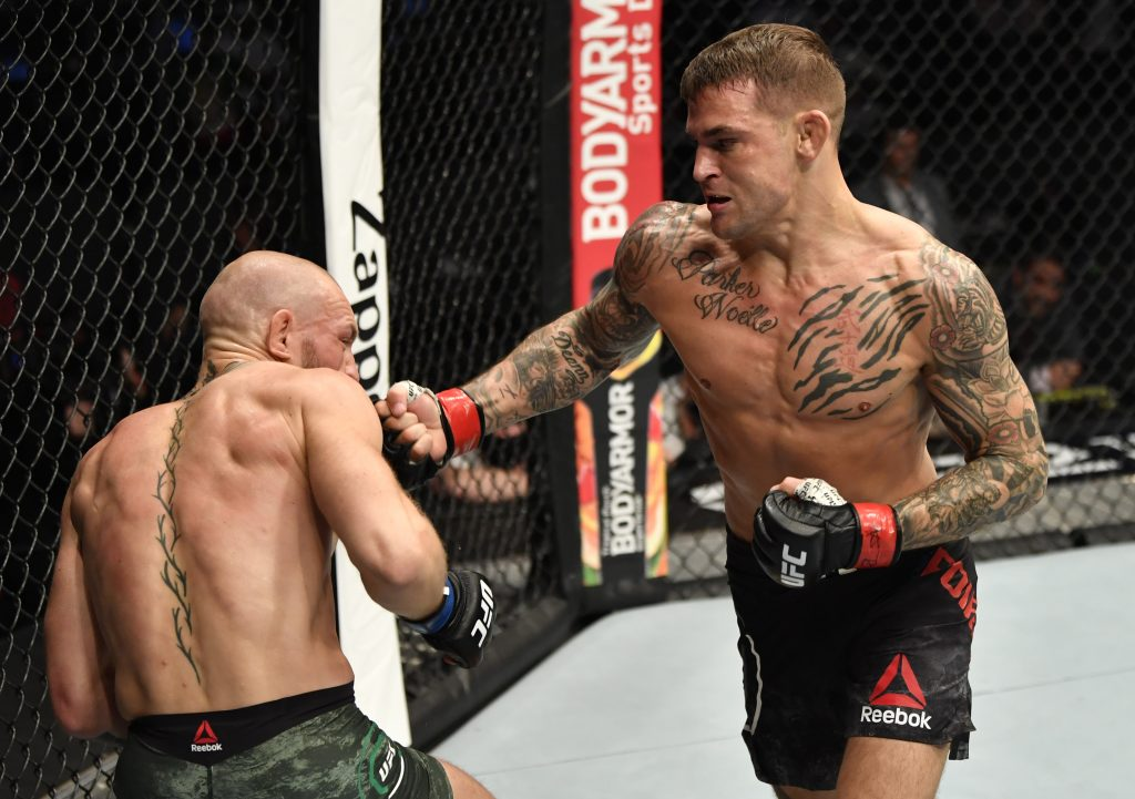Dustin Poirier punches Conor McGregor of Ireland in a lightweight fight during the UFC 257 event. (Photo by Jeff Bottari/Zuffa LLC via Getty Images)